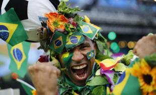 Un supporter de soccer brésilien couvert de fleurs et arborant le drapeau de son pays dans une aire du Fan Fest de la FIFA avant le début du match d'ouverture de la Coupe du Monde entre le Brésil et la Croatie à Rio de Janeiro, au Brésil, le 12 juin 2014. Après avoir mené le début de ce match, la Croatie a perdu 3-1 contre le Brésil, cinq fois champion du grand tournoi international de soccer. (Photo AP/Silvia Izquierdo)