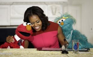 La première dame des États-Unis, Michelle Obama, au centre, avec Elmo, à gauche, et Rosita, à droite, tandis qu'ils aident à promouvoir la consommation de fruits et légumes frais parmi les enfants, le 30 octobre 2013. (AP Photo/Pablo Martinez Monsivais)