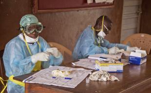 Des travailleurs de la santé portant des vêtements et des accessoires de protection contre le virus Ebola sont assis à un bureau de l'hôpital public de Kenema en Sierra Leone en août 2014. (AP Photo/ Michael Duff)