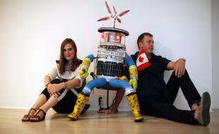 Le jeudi 21 août 2014, à Victoria en C.-B., hitchBOT pose avec ses co-créateurs Frauke Zeller, professeure adjointe à l'Université Ryerson et David Smith, professeur au département d'études en communication de l'Université McMaster. (La Presse canadienne/Chad Hipolito)