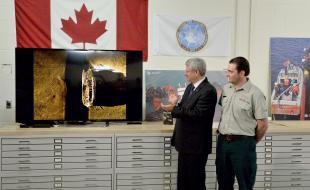 Le 9 septembre 2014, le premier ministre Stephen Harper acclame la découverte, par l'Expédition du détroit de Victoria, de l'épave d'un des navires de l'Expédition arctique catastrophique de 1845 dirigée par Sir John Franklin, tandis que Ryan Harris, de Parcs Canada, examine l'image du navire. (LA PRESSE CANADIENNE/Sean Kilpatrick)