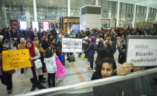 Des membres de groupes qui parrainent deux familles de réfugiés syriens tiennent des pancartes leur souhaitant la bienvenue tandis qu'ils attendent leur arrivée à l'Aéroport Pearson de Toronto, le 9 décembre 2015. (LA PRESSE CANADIENNE/Chris Young)