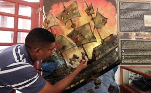 Un monsieur montre du doigt une illustration du galion espagnol San José au cours d'une conférence de presse annonçant, en décembre, la découverte de son épave près de Carthagène, Colombie. [Photo avec la permission d'EPA/RICARDO MALDONADO ROZO.]