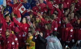 Penny Oleksiak, qui porte le drapeau canadien, s'apprête à participer, avec ses coéquipières, aux cérémonies de clôture des Jeux olympiques de Rio de Janeiro, au Brésil, le 21 août 2016. (LA PRESSE CANADIENNE/HO - COC - Jason Ransom)