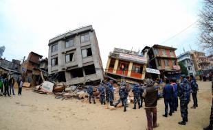 Des soldats et des résidents locaux inspectent les décombres de bâtiments dévastés par un puissant séisme à Katmandou, Népal, le 26 avril 2015. (Photo de Sunil Pradhan/Anadolu Agency/Getty Images)